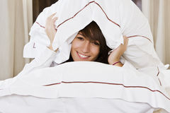 Smiling woman between pillows Royalty Free Stock Image
