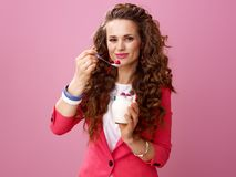 Smiling woman on pink background eating farm organic yogurt. Pink Mood. Portrait of smiling young woman with long wavy brunette hair on pink background eating Royalty Free Stock Photography