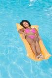 Smiling woman in pink bikini lying on lilo in swimming pool Royalty Free Stock Photo