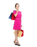 Smiling woman in pink dress with shopping bags Royalty Free Stock Image