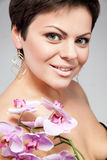 Smiling woman with pink orchid Royalty Free Stock Photo