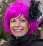 Smiling woman with a pink wig and a black flower. Royalty Free Stock Photography