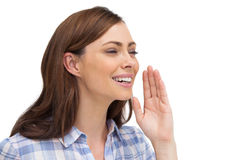 Smiling woman placing her hand to say something. On white background Royalty Free Stock Image