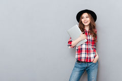 Smiling woman in plaid shirt holding laptop and looking away Royalty Free Stock Photography