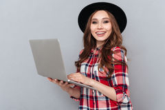 Smiling woman in plaid shirt holding laptop Stock Photography