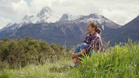 Smiling woman in plaid shirt is sitting on a green meadow against mountains at sunny day. Alps mountains. 4k stock video footage