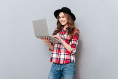 Smiling woman in plaid shirt standing and working on laptop Royalty Free Stock Photography