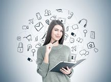Smiling woman with a planner, modern communication. Smiling young woman wearing a gray sweater is holding a planner and a pen. A gray wall with a social media stock photography