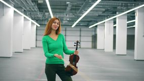 Smiling woman is playing with the bow and the violin. 4K stock video footage