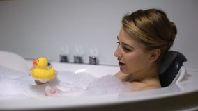Smiling woman playing with rubber duck in bath, childish mood, having fun stock video