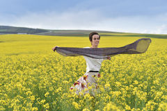 Smiling woman playing with scarf in a canola field Stock Photo