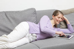Smiling woman playing using her tablet-pc Royalty Free Stock Image