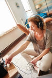 Smiling woman plugging in headphones into sound system. Portrait of smiling woman plugging in headphones into sound system Stock Photography