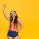 Smiling Woman Is Pointing Above Head And Looking Up Royalty Free Stock Images