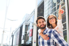 Smiling woman pointing away while enjoying piggyback ride on man in city Stock Images