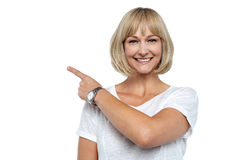 Smiling woman pointing backwards Royalty Free Stock Photos