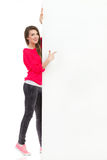 Smiling woman pointing at big empty banner Royalty Free Stock Photos