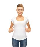 Smiling woman pointing at blank white t-shirt stock photography