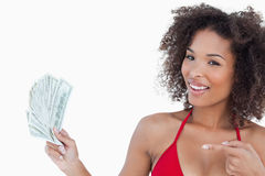 Smiling woman pointing a fan of notes Stock Photos