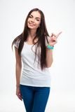 Smiling woman pointing finger away. Smiling beautiful woman pointing finger away isolated on a white background Stock Photo