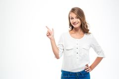 Smiling woman pointing finger away. Smiling casual woman pointing finger away isolated on a white background Stock Images