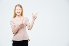Smiling woman pointing finger away Stock Image