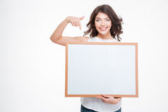 Smiling woman pointing finger on blank board Royalty Free Stock Photo