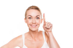 Smiling woman pointing with her finger Royalty Free Stock Photography