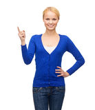 Smiling woman pointing her finger up Royalty Free Stock Photos