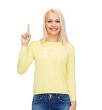 Smiling woman pointing her finger up Stock Photography
