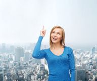 Smiling woman pointing her finger up Royalty Free Stock Images