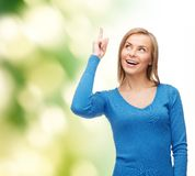 Smiling woman pointing her finger up Stock Images