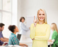 Smiling woman pointing her finger up Royalty Free Stock Image
