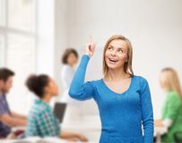 Smiling woman pointing her finger up Stock Photos