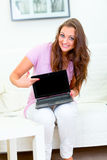 Smiling woman pointing in laptops blank screen Stock Photo