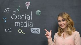 Smiling woman pointing at social media phrase on blackboard, modern technologies. Stock footage stock video