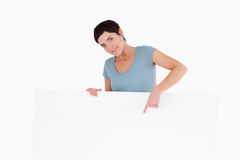 Smiling woman pointing at something on a panel Royalty Free Stock Image