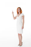 Smiling woman pointing to blank copyspace. Smiling attractive redhead woman in a simple white dress and high heels standing pointing upwards to blank copyspace Stock Photos