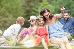 Smiling woman pointing to daughter while sitting on pier against family at lakeshore during summer stock image