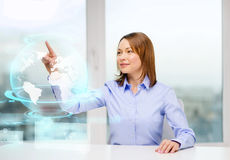 Smiling woman pointing to earth hologram Royalty Free Stock Image