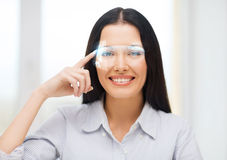 Smiling woman pointing to futuristic glasses Stock Photos
