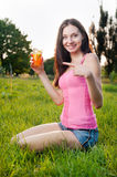 Smiling woman pointing to glass of orange juice Royalty Free Stock Photography