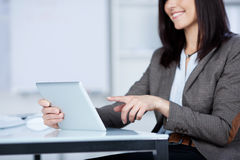 Smiling woman pointing to her tablet Royalty Free Stock Photo