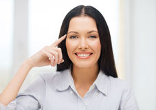 Smiling woman pointing to imaginy glasses Stock Image