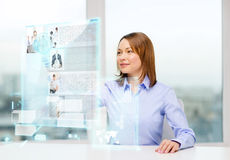 Smiling woman pointing to news on virtual screen Stock Photography