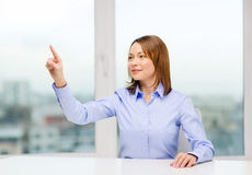 Smiling woman pointing to something imaginary Stock Images