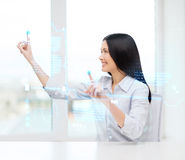 Smiling woman pointing to virtual screen Stock Photo