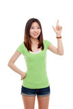 Smiling woman pointing up. Smiling Asian woman pointing up isolated on white background Royalty Free Stock Photos