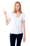 Smiling woman pointing up with her finger Royalty Free Stock Photos