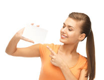 Smiling woman pointing at white blank card Royalty Free Stock Photos